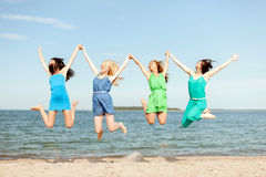 Smiling girls jumping on the beach Stock Image