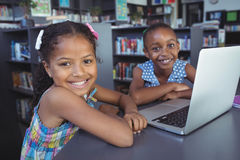 Smiling girls with laptop at desk in library. Portrait of smiling girls with laptop at desk in library Stock Photography