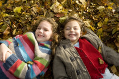 Smiling girls laying in autumn leaves.  Royalty Free Stock Photography