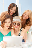 Smiling girls looking at tablet pc in cafe Royalty Free Stock Photography