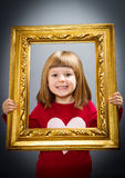 Smiling girls looking through a vintage picture frame Royalty Free Stock Images