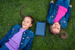 Smiling girls lying on grass with digital tablet Stock Image