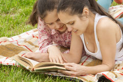 Smiling girls outdoor reading book stock image