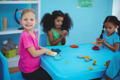 Smiling girls playing with modelling clay Stock Images