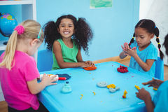 Smiling girls playing with modelling clay Stock Photos