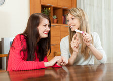 Smiling girls with pregnancy test. At table in living room stock images