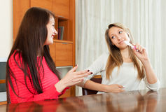 Smiling girls with pregnancy test at table. In room. Focus on brunette stock photos