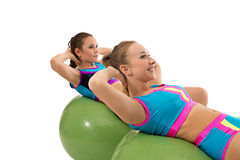 Smiling girls pump abdominals on fitness balls Stock Photography