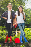 Smiling girls in rubber boots posing at garden with shovel Stock Photography