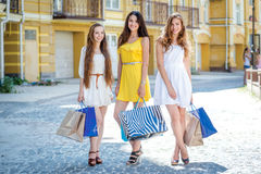 Smiling girls shopaholics. Girls holding shopping bags and walk Stock Images