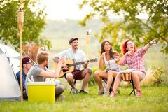 Smiling girls show something in distance in campground Royalty Free Stock Photos