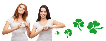 Smiling girls showing heart gesture with shamrock Stock Photography