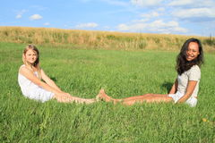 Smiling girls sitting on grass royalty free stock photography