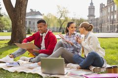Smiling girls sitting near busy fellow student. Busy student. Smiling pretty girls sitting near their busy fellow student preparing for important test Royalty Free Stock Photo