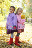 Smiling girls standing back-to-back in autumn park Stock Photography