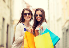 Smiling girls in sunglasses with shopping bags Royalty Free Stock Photos