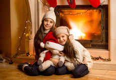 Smiling girls in sweater and hats warming up at fireplace at Chr Royalty Free Stock Photo