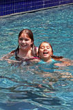Smiling girls in swimming pool. Two girls (ages 6 and 11) having fun in a swimming pool. They have brown eyes and hair and are of Asian and Caucasian background Royalty Free Stock Images
