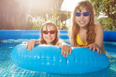 Smiling girls swimming in pool with  rubber ring Stock Photos