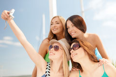 Smiling girls taking photo in cafe on the beach Stock Photography
