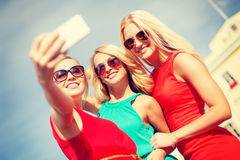 Smiling girls taking photo with smartphone camera Royalty Free Stock Image