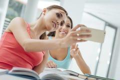 Smiling girls taking selfies at school Royalty Free Stock Photos