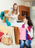 Smiling  girls together looking purchases Royalty Free Stock Photo