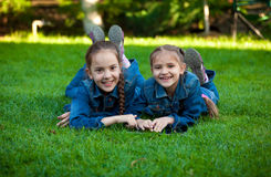 Smiling girls using tablet while lying on grass at yard Stock Image