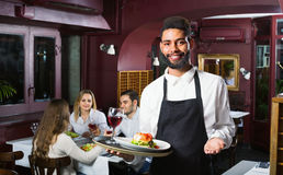 Smiling glad waiter taking care of adults. Smiling glad  waiter taking care of adults at cafe table Stock Images