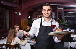Smiling glad young waiter taking care of adults Stock Photos
