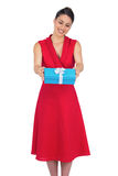 Smiling glamorous model in red dress offering present Stock Photo