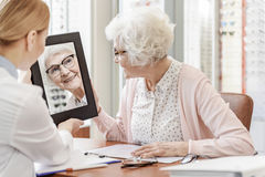 Smiling glance of old lady. Happy mature women wearing glasses is looking at her reflection. Shop assistant holding mirror. They are sitting near table Royalty Free Stock Image