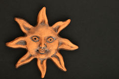 Smiling glazed ceramic sun souvenir isolated on black Stock Photo