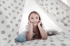 Smiling gleeful girl lying on bed stock images