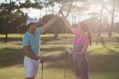 Smiling golf player couple giving high five. While standing on field Stock Photos