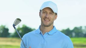 Smiling golf player holding iron club posing to camera, hobby, leisure activity. Stock footage stock video