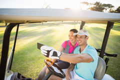Smiling golfer couple taking selfie. While sitting in golf buggy royalty free stock images