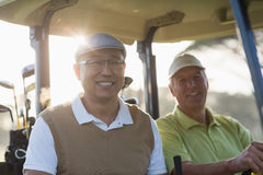 Smiling golfer friends sitting in golf buggy Royalty Free Stock Photo