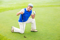 Smiling golfer kneeling on the putting green Royalty Free Stock Images