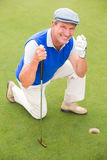 Smiling golfer kneeling on the putting green Royalty Free Stock Photography