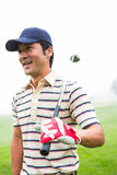 Smiling golfer standing and holding his club. At the golf course Stock Photo