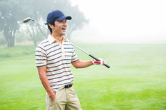 Smiling golfer standing and holding his club. At the golf course Stock Photos