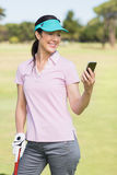 Smiling golfer woman using phone Royalty Free Stock Image