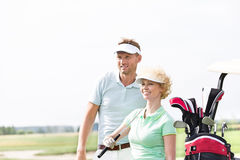 Smiling golfers standing at golf course against clear sky Royalty Free Stock Photo