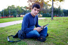 Smiling good looking man with tablet in park Royalty Free Stock Images