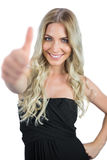 Smiling gorgeous blonde in black dress thumbs up Stock Images