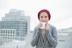Smiling gorgeous blonde holding coffee outdoors Stock Image