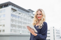 Smiling gorgeous blonde with red lips holding tablet Royalty Free Stock Photo