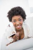 Smiling gorgeous brunette holding smartphone Stock Image