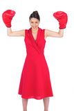 Smiling gorgeous brunette in red dress wearing boxing gloves Royalty Free Stock Photos